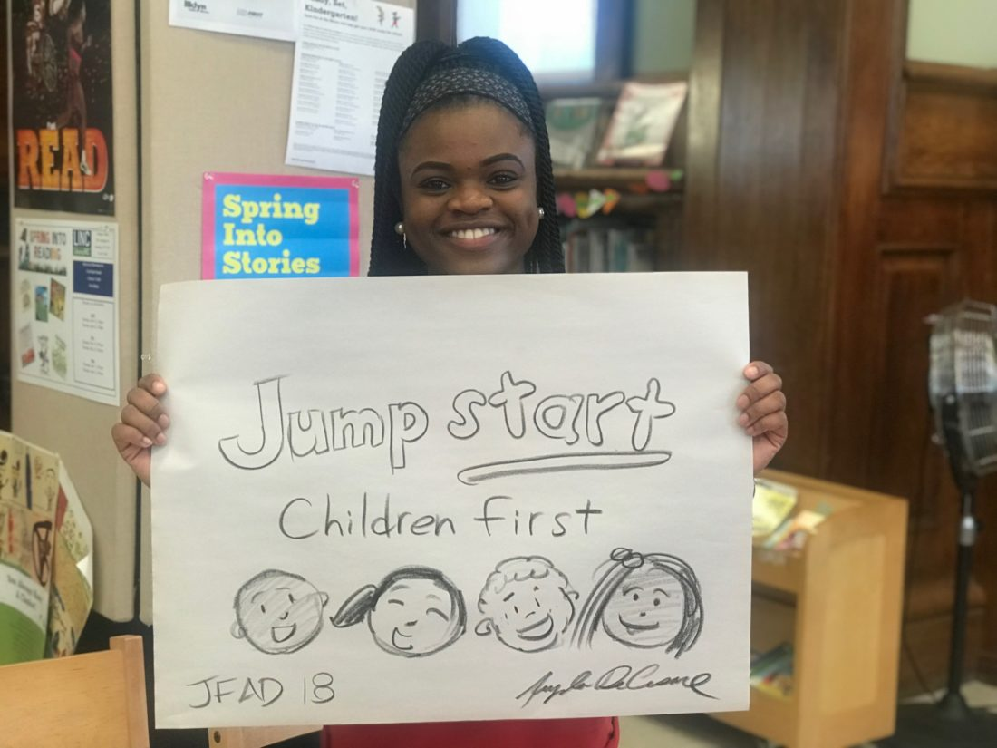 """Kayla Jones smiling and holding a handmade sign which reads """"Jumpstart, Children first"""" and drawn pictures of smiling kids faces"""