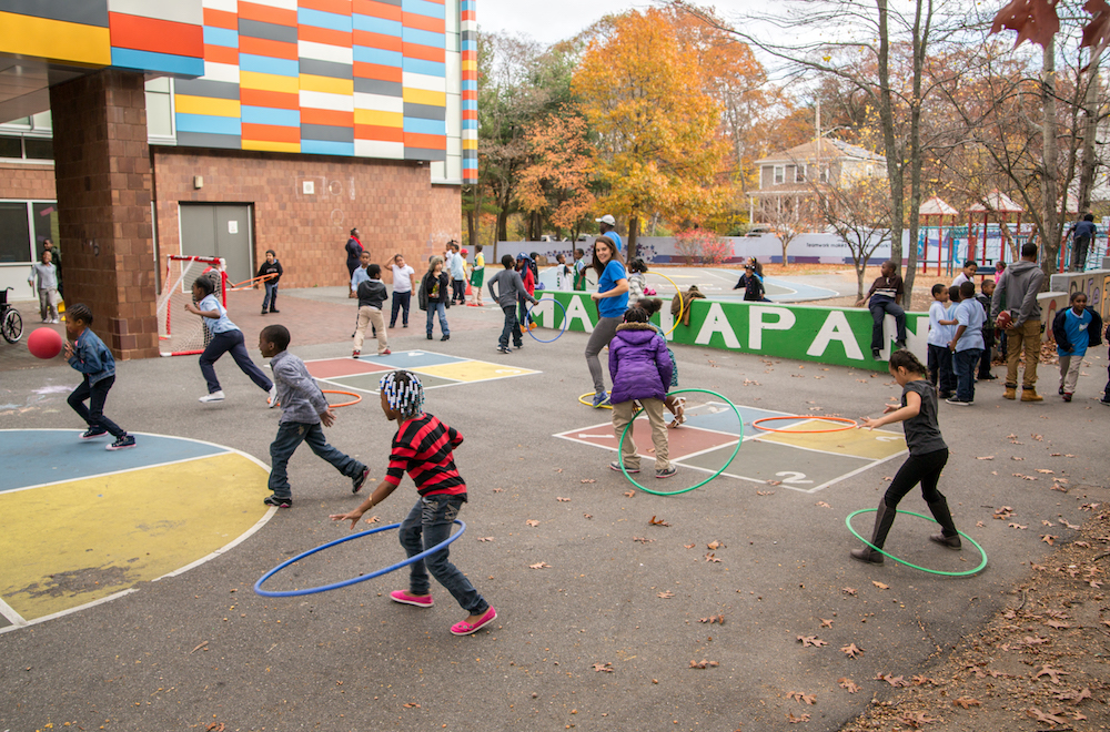 Children playing with hula hoops and basketballs at recess