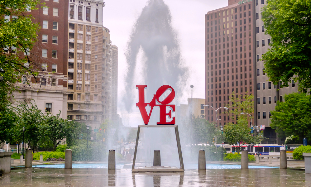 Love Statue in Philadelphia, with scenic fountain against a cloudy sky.