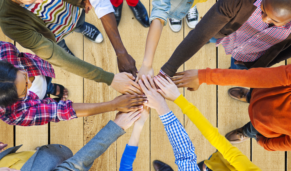 People put their hands together in a circle in a show of collaboration and teamwork