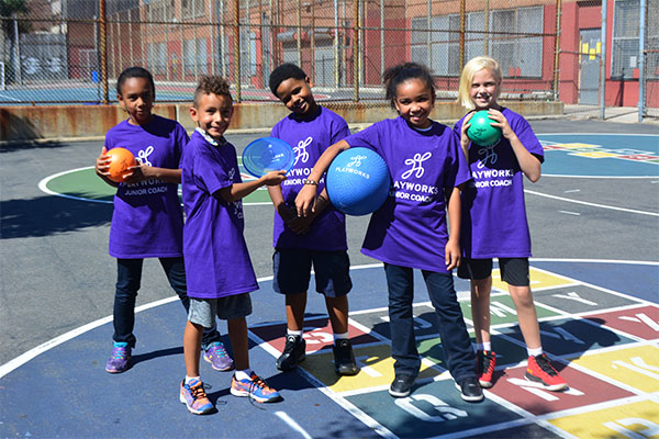 Five children in Playworks shirts on a playground at recess