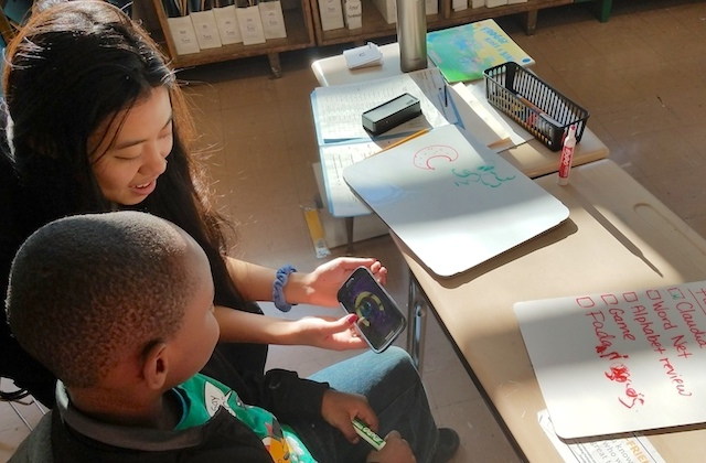 Woman shows a child something on a phone in a classroom.