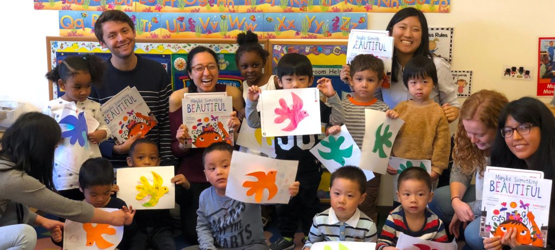 FAO Schwarz Fellows in a classroom with a group of y oungchildren holding colorful art projects