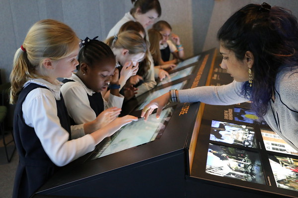 A fellow works with students in a museum
