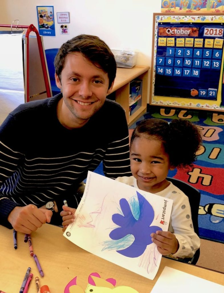 A former fellow poses with a young student in a classroom, who is holding up a piece of art she created.
