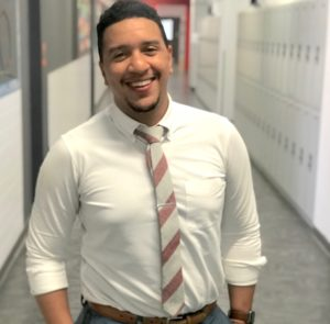 Jonathan Baez stands in a school hallway and smiles at the camera