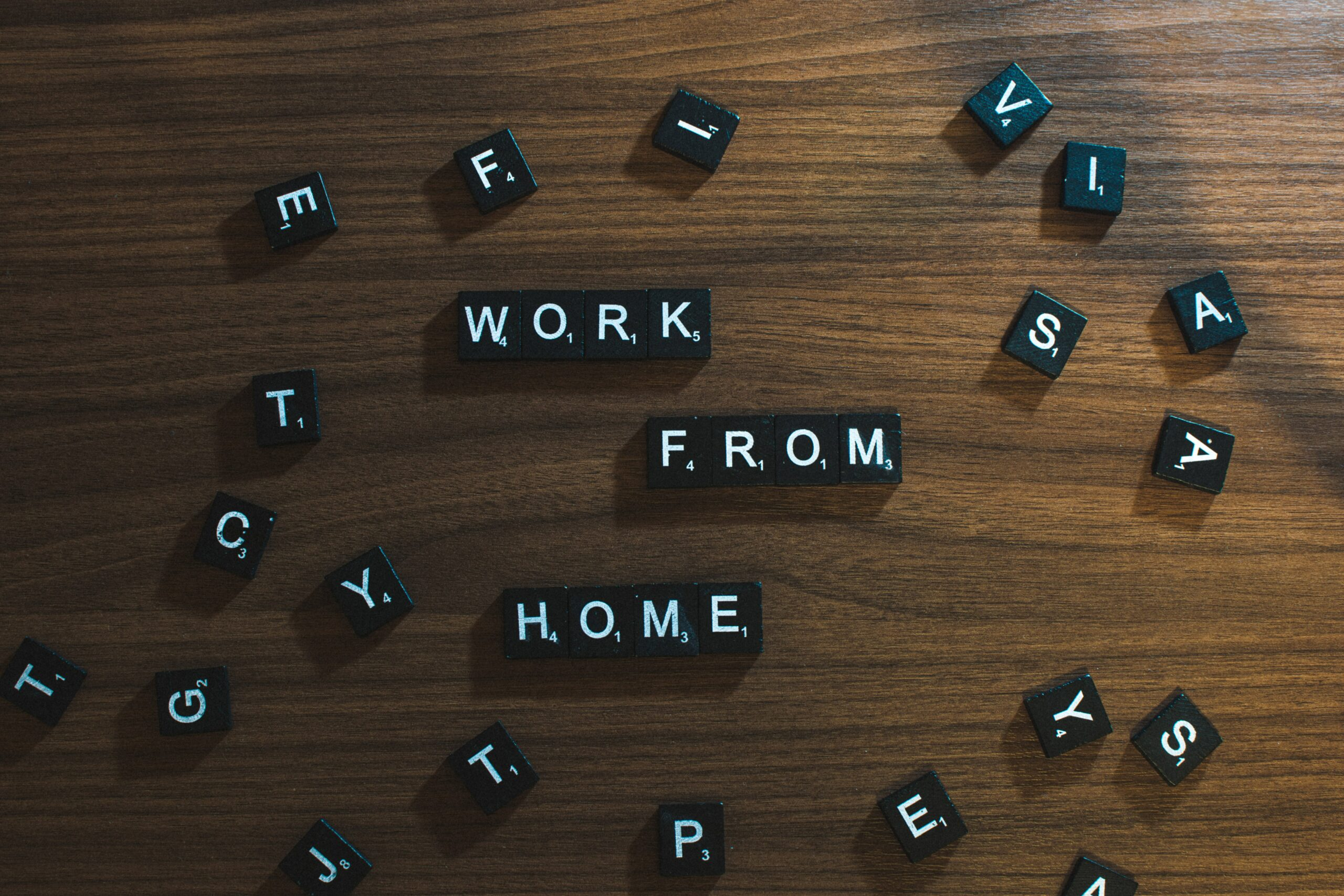 Black tiles with white letters spelling out Work From Home on a brown background