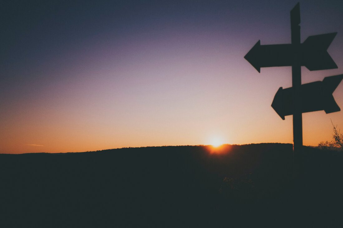 Silhouetted sign post with arrows in front of sunset