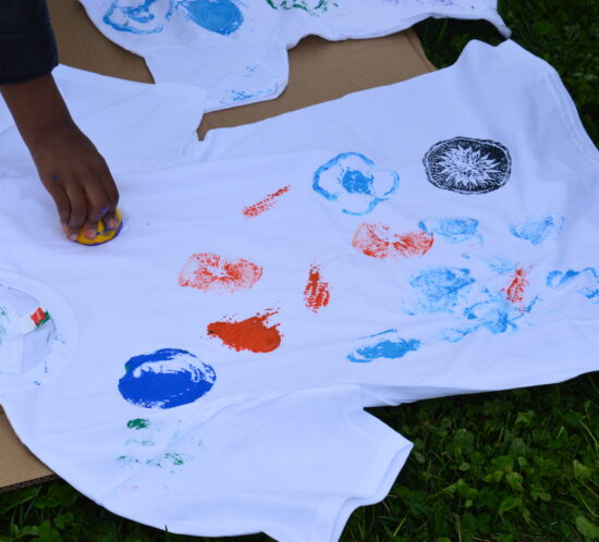 A child's hand is shown stamping a pattern on a white t-shirt.
