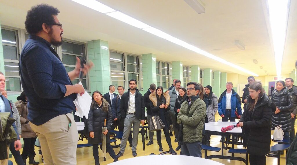 A person speaking in front of a crowd in a cafeteria